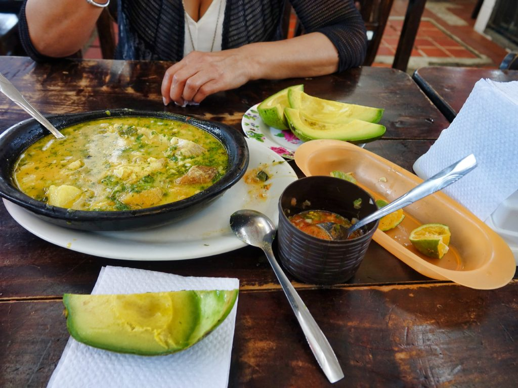 Sancocho de Pescado and lemon, hot sauce, and Aguacate (avocado)